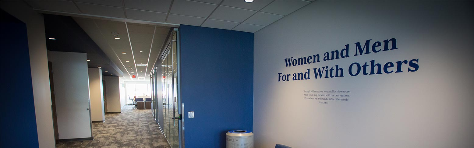Women and men for and with others tagline on wall