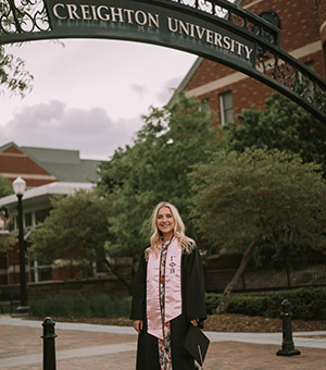Mary Ascher in graduation robe on Creighton campus